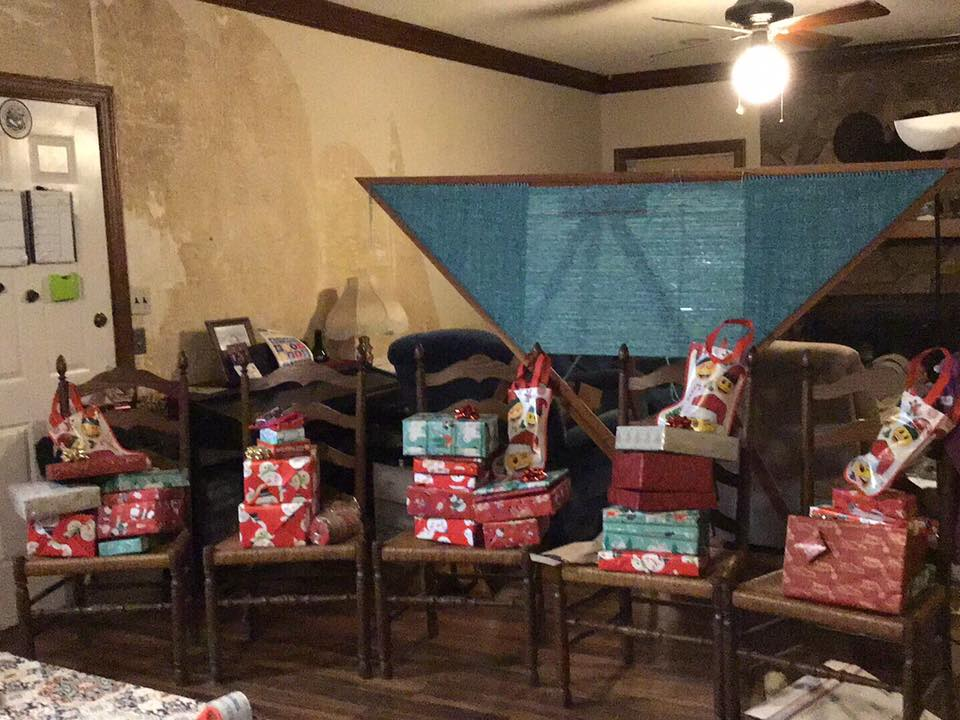 piles of wrapped gifts and stockings on chairs